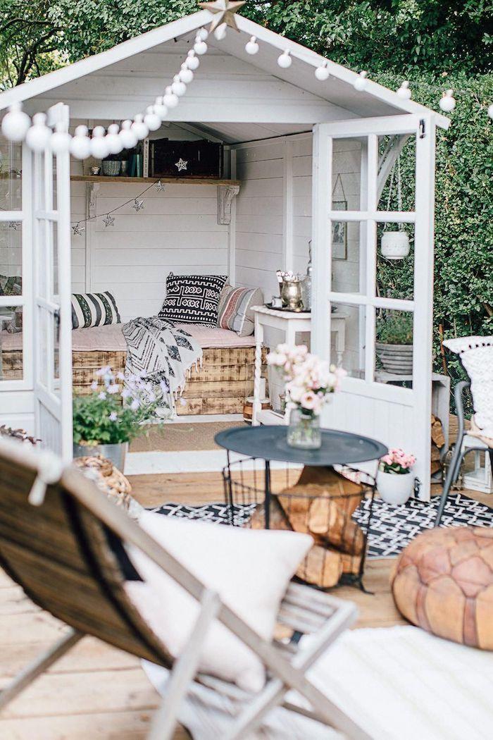 mini holz gartenhaus terrasse häuschen mit bett aus holz runder korbtisch schwarz weiß schwarzer teppich boho chic stil außeneinrichtung