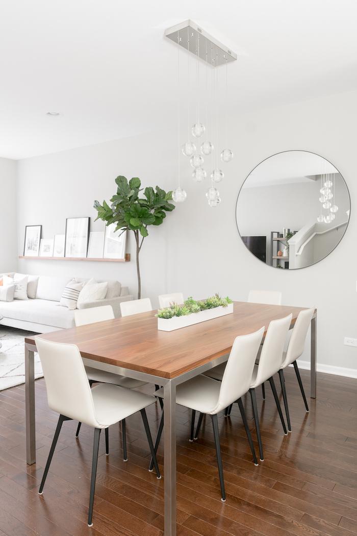 minimalistische inneneinrichtung in weiß kombiniertes wohn esszimmer einrichten großer runder spiegel grüne pflanze moderne einrichtung esszimmer dunkler holzboden