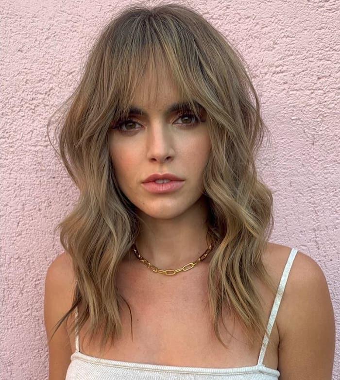 mittellanger shag haircut mit pony braune haare mit blonden strähnen goldene halskette wießes sommertop moderne haarschnitte inspiration