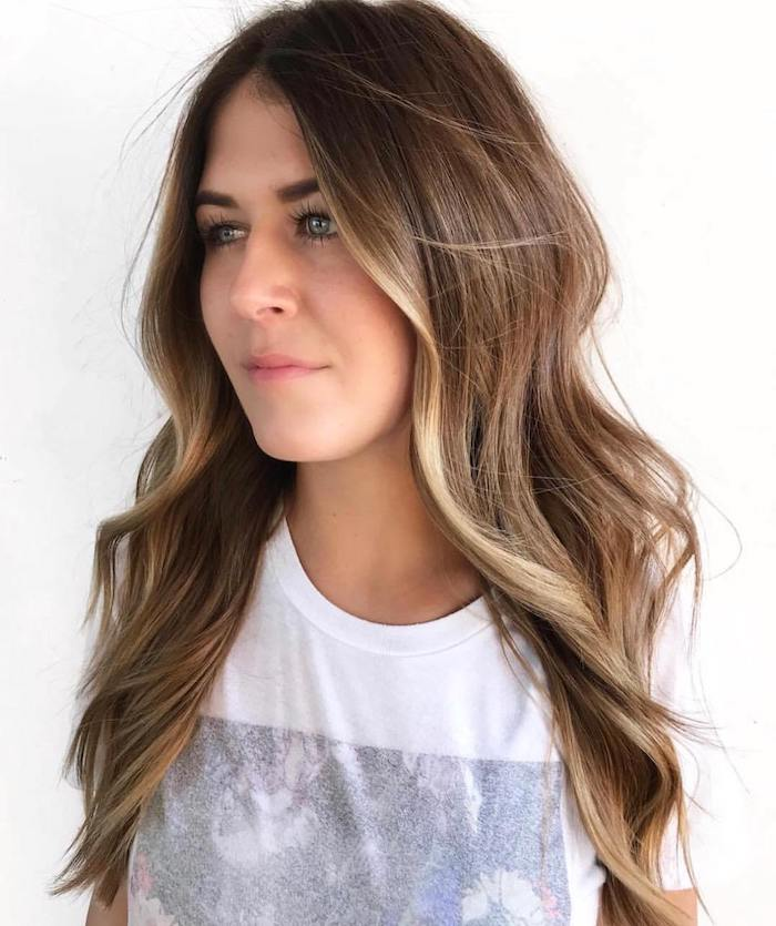 mocha welle mit balayage haarfarbe braune haare mit strähnen weißes t shirt mit print frau mit langen gewellten haaren haarfarbe inspo