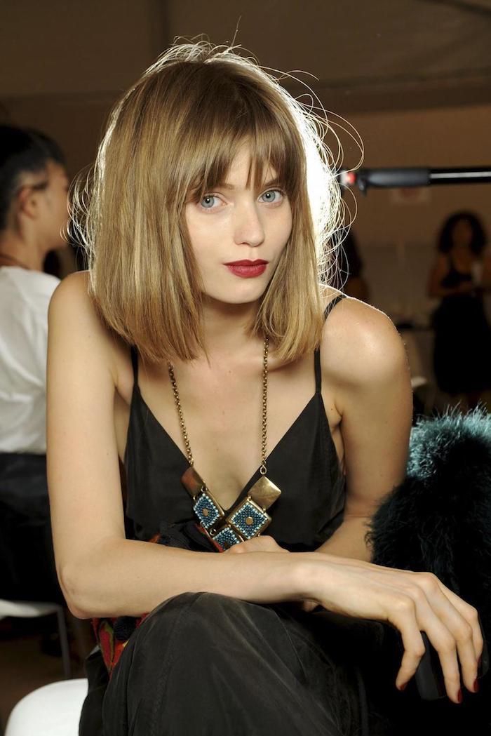 model fashion show dunkel blonde pony haare kurzer haarschnitt langes schwarzes boho kleid mit maxi halskette roter lippenstifft frau mit blauen augen