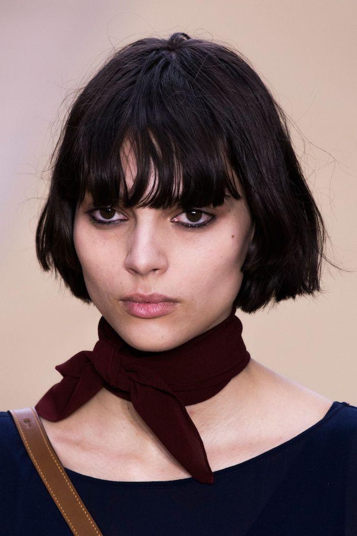 modeschau fashion week paris model mit schwarzen kurzen haaren bob frisuren 2021 mit pony französischer stil eleganter schal gebunden um den hals