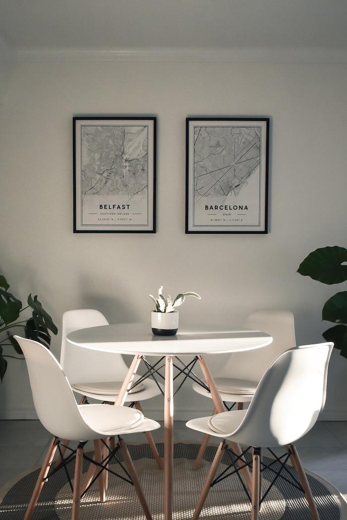 monochrome minimalistische einrichtung kleiner runder tisch mit vier stühlene bilder an die wand mit karten von belfast und barcelona wohn esszimmer einrichten