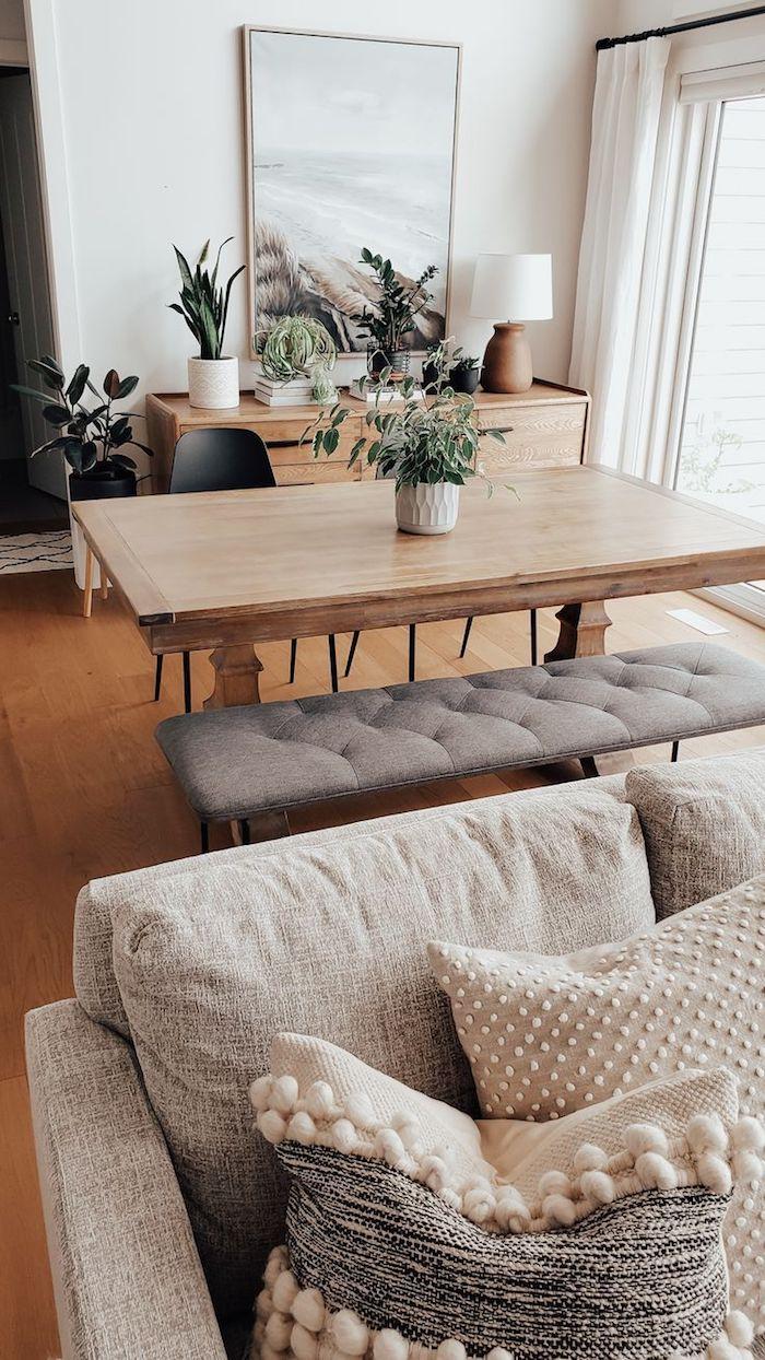 offenes konzept wohnzimmer mit essbereich minimalistische farben holz motive grüne pflanzen großes gemälde vom strand