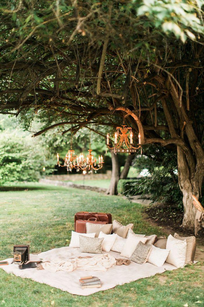 orange kronleuchter aufgehängt an einem baum romantischer picknick im garten schöne gärten bilder weiße decke große und kleine kissen