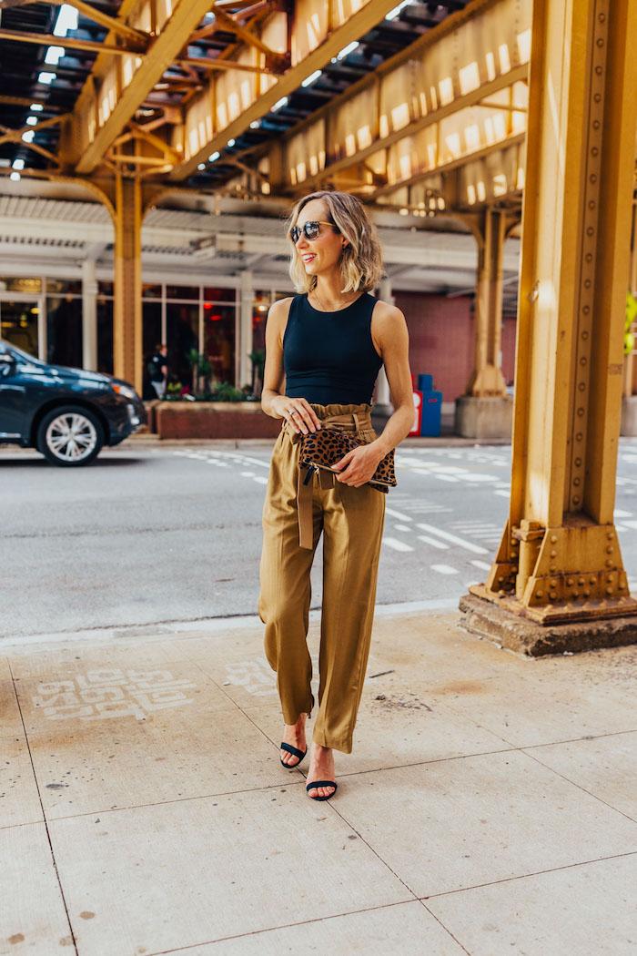 paperbag hose beige stylen mit schwarzem top kleine tasche mit leopard print schwarze high heels dame mit kurzen blonden haaren