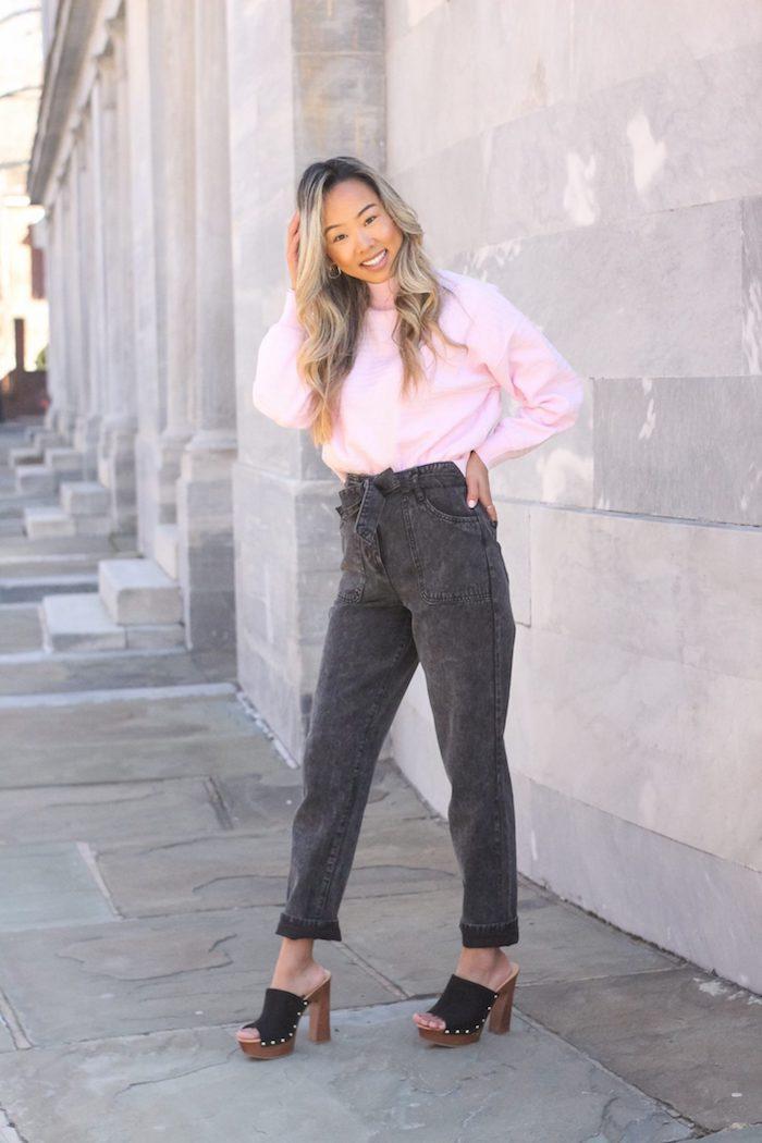paperbag hose schwarz jeans kombiniert mit pinkem pullover clogs holzschuhe mit absatz damen mit langen gewellten haaren schwarze haare mit blonden highlights