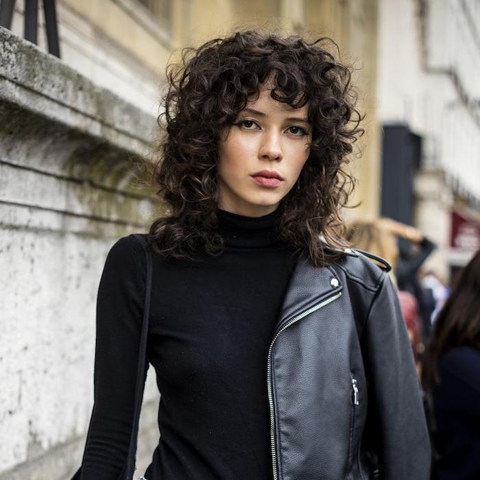 paris fashion week street style casual outfit schwarze lederjacke und rollkragenpulli shaggy frisur mittellang mit natürlichen locken dunkle haare