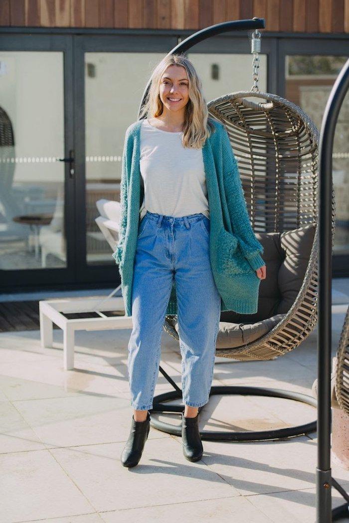 schwarze boots mit absatz paperbag hose kombinieren lange blaue strickjacke weißes basic t shirt mittellange blonde haare gewellt