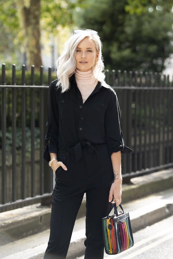 schwarzes outfit mit beigem rollkragenpullover mini bunte tasche street style inspo haarschnitt mittellang mit wellen
