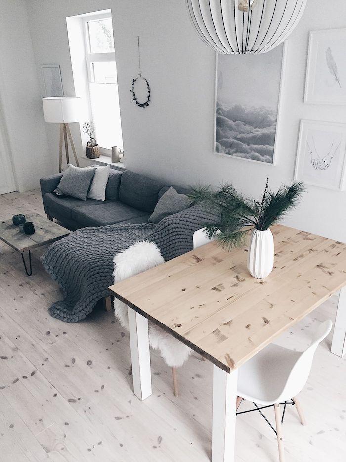 skandinvische einrichtung minimalistisch kombiniertes wohn esszimmer einrichten grauer ecksofa flauschige decke und kissen heller holztisch weiße stühle kreative wandgestaltung wohnzimmer