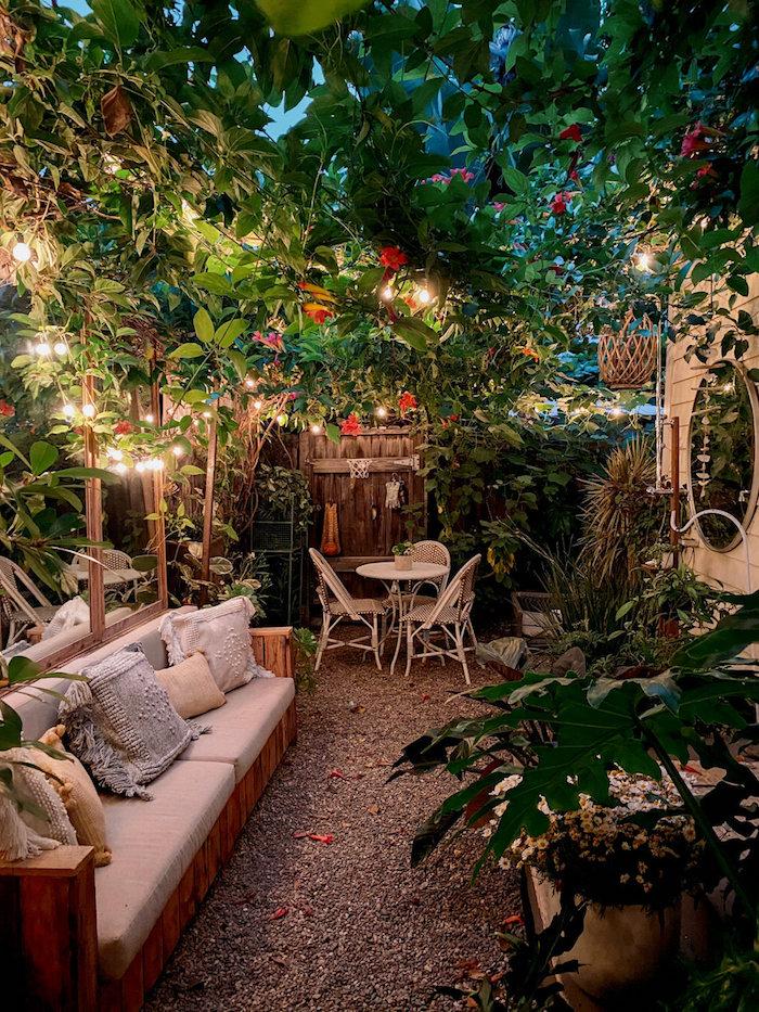 sommer garten ideen einfach einrichtung mit vielen pflanzen gartenmöbel couch weißer runder tisch mit stühlen kleine hängeleuchten