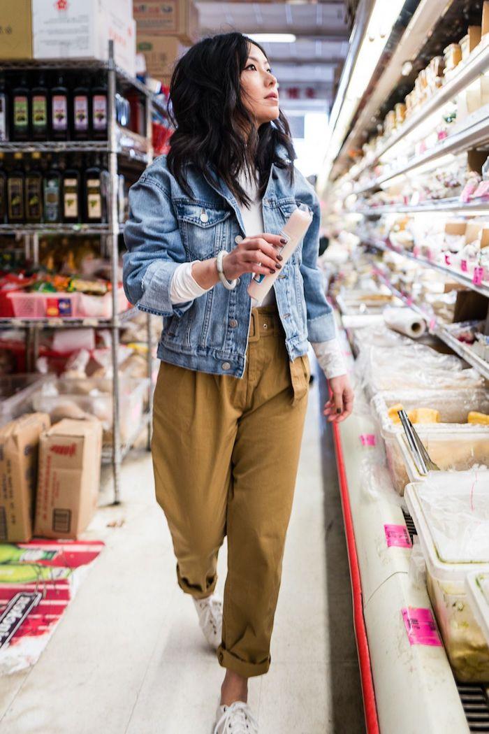 sportlich elegantes outfit weiße sneakers paperbag hose beige kombiniert mit blauer jeansjacke foto im supermarkt frau mit schwarzen haare