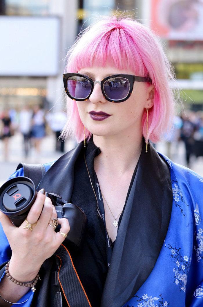 street style fotografie blauer blazer mit kleinen blumen coole pinke pony haare große runde schwarze sonnenbrillen frau hält kamera in der hand