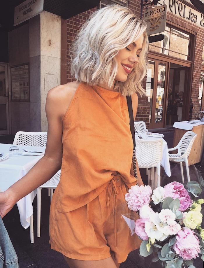 street style inspiration oranges outfit aus top und kurzen hosen hellblonde gewellte haare blunt cut haarschnitt schöne blumen frühling