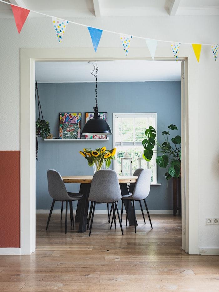 stylische esszimmer ideen kleine wohnung einrichten runder tisch aus holz graue stühle grau blaue wandfarbe große grüne pflanze sonnenblume in vase