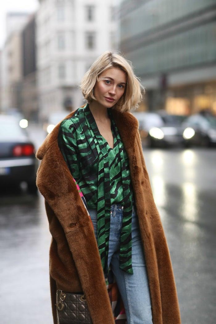 stylishe grüne bluse mit schwarzen streifen blaue jeans brauner pelzmantel street style new york blunt cut blonde haare kurze frisuren ideen