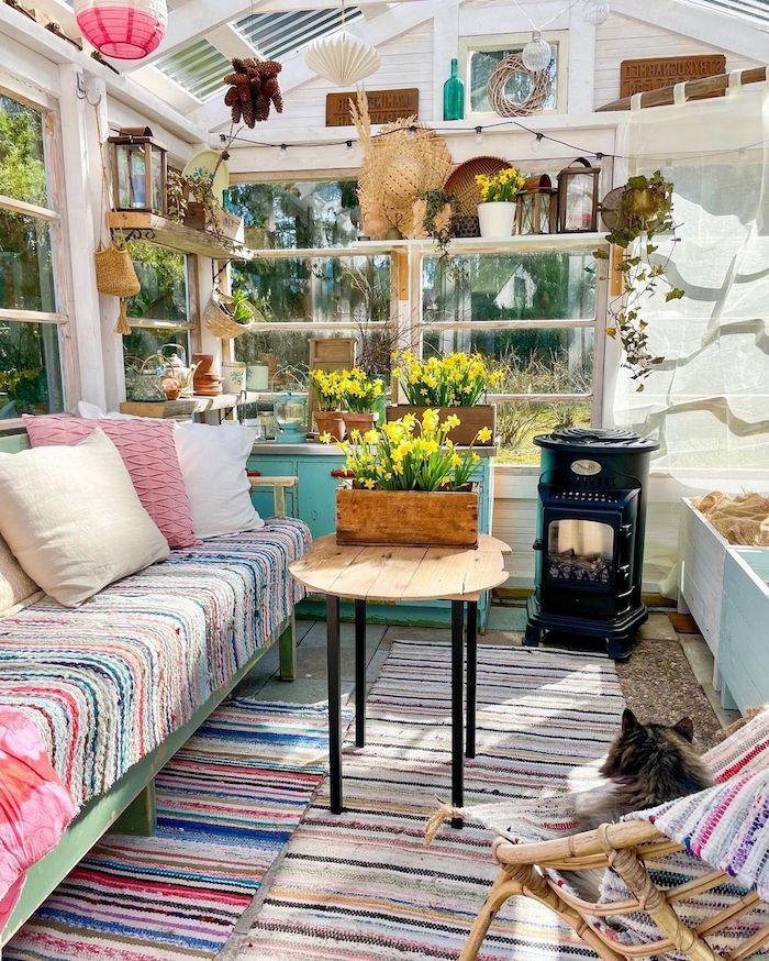 süßes holzhaus garten renoviert in einem wohnzimmer bunte decke auf dem sofa kaffeetisch aus holz gelbe blumen kleiner ofen