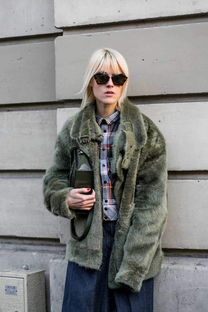 trendiger street style grüner flauschiger mantel dunkle jeans shaggy bob 2021 mit pony hellblonde haare schwarze sonnenbrillen