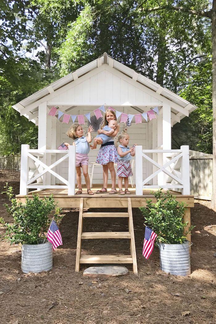 vier kleine kinder gartenhäuser aus holz modern einrichten für kinder weißes haus deko fahnen in blau und rot