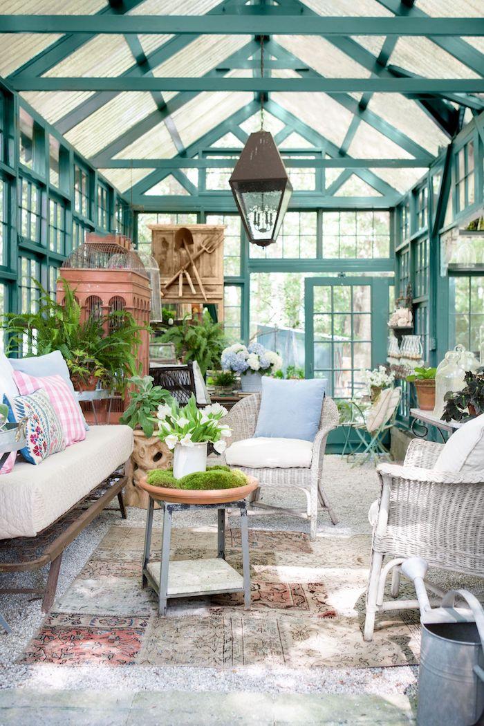 vintage inneneinrichtung gartenschuppen gartenhäuser aus holz in grün sofa mit weißer polsterung gewebte stühle blaue kissen persischer teppich