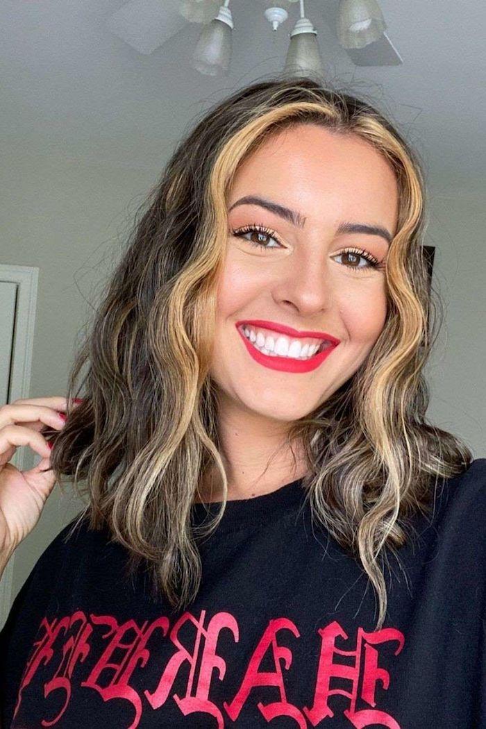 vorne blonde strähnen auf braune haare lächelnde junge frau roter lippenstift schwarzes t shirt mit print moder frisuren und haarfarben