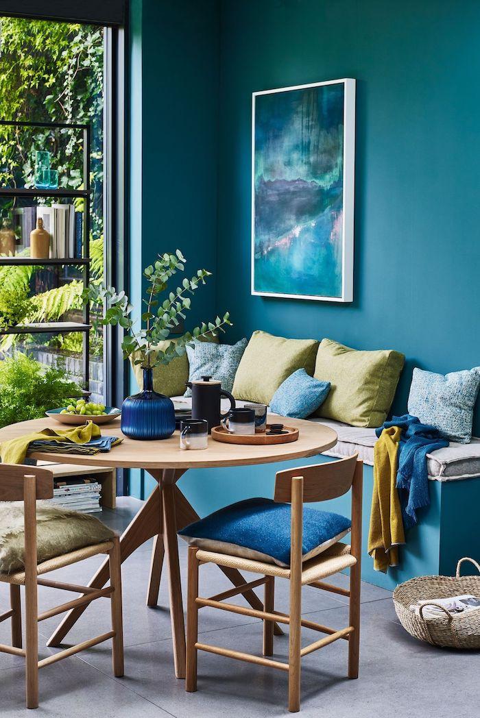 wandfarbe aquamarien blaues gemälde grüne kissen runde tisch und stühle aus holz stylische esszimmer ideen