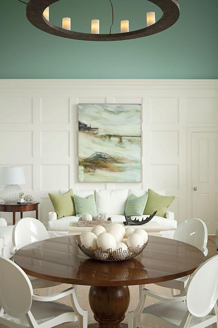 wandfarbe weiß grün wohnzimmer mit essbereich runder tisch aus holz weiße stühle weißes sofa mit grünen und weißen kissen moderne inneneinrichtung