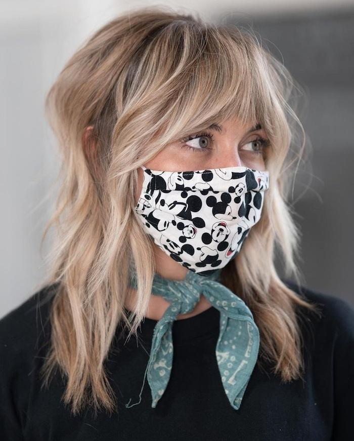 weiße maske mit mickey mouse grüner schal als accessoire am nacken blonde frau mittellanger haarschnitt shaggy mullet frisur inspiration