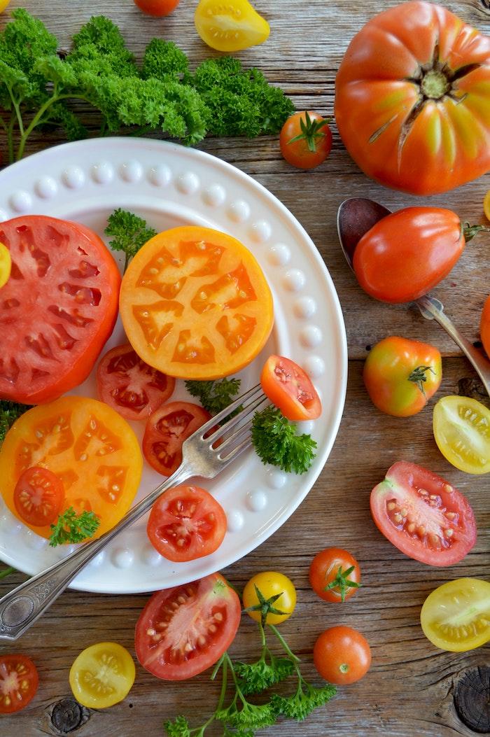 weißer teller mit geschnittenen roten tomaten ein tisch aus holz rote tomaten salat zum grillen schnell gemacht