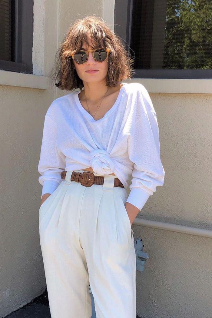 weite weiße geknotete bluse weite hosen mit braunem gürtel runde sonnenbrillen street style inspo lockige pony haare kurzhaarfrisuren ideen
