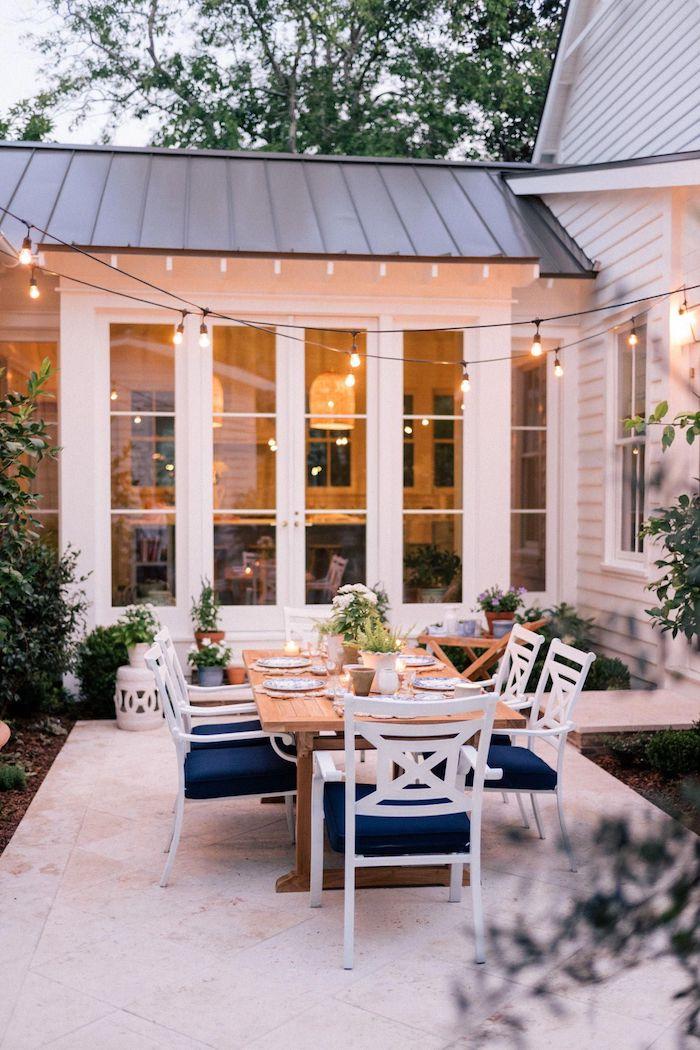 wie kann ich meinen garten romantisch gestalten weiße gartenstühle mit blauen kissen großer langer tisch aus holz kleine hängeleuchten schön gedeckter tisch schöne gärten bilder