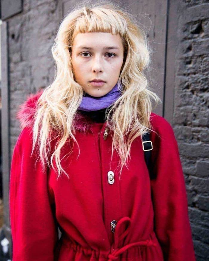 winter mode frau im roten mantel und.lila schal lange blonde haare mit kurzem pony modern shag lang und gewellt