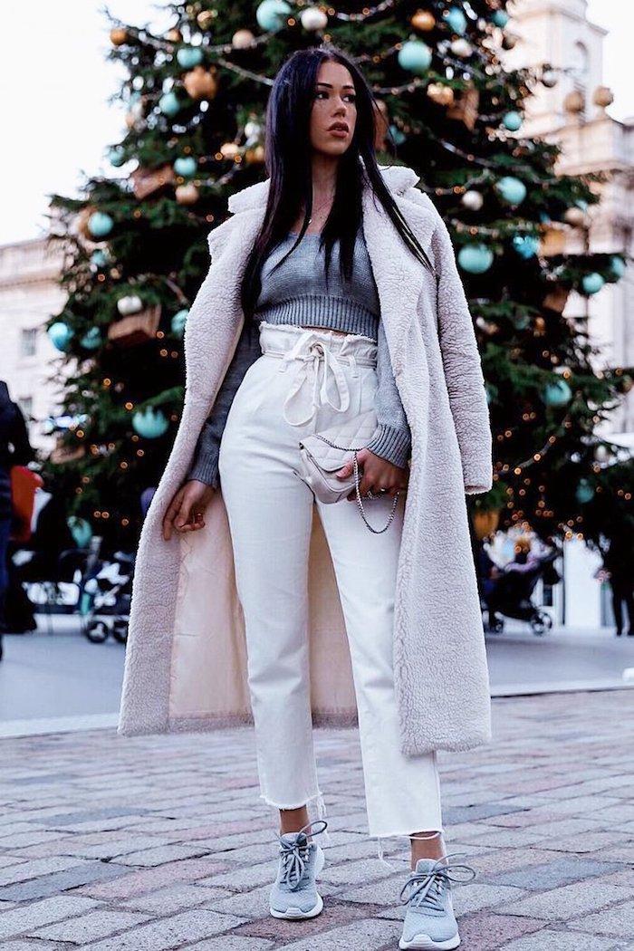 winter outfit weißer flauschiger mantel graue gecroppte bluse was ist eine paperbag hose sportliche sneaker großer tannenbaum im hintergrund