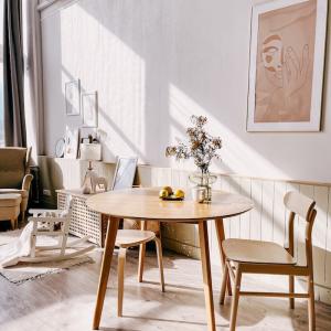 wohnung einrichten wohnzimmer mit essbereich gestalten kleiner runder tisch und stühle aus holz minimalistische wandgestaltung modernes gemälde