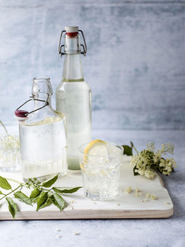 zwei flschen aus glas ein brett aus holz holunderblütensirup selber machen ein glas mit zitronen und eis