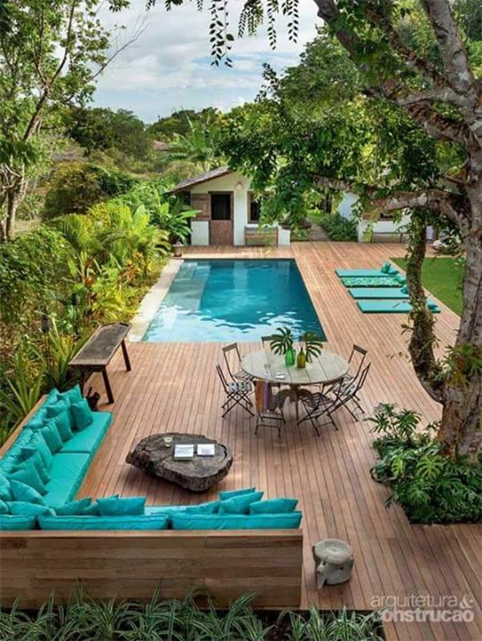 außeneinrichtung ideen und inspirartion großes ecksofa mit blauen kissen runder esstisch terrasse aus holz pool garten inspo