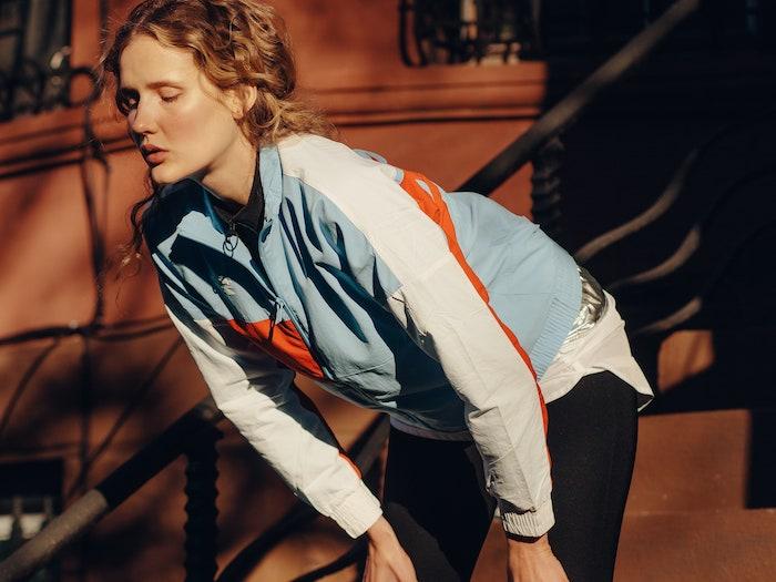 blonde frau macht pause nach dem jogging bunte sport jacke schwarze leggins was hilft gegen muskelkater tipps und info