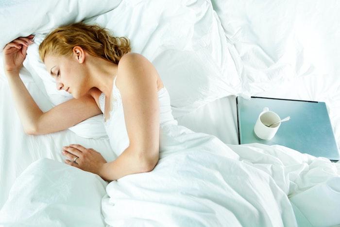 blonde frau schläft im bett weiße bettwäsche kliene kaffeetasse was kann man gegen schnarchen machen ideen für heilmittel
