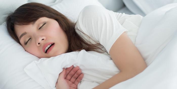 braune haare frau schläft im bett weiße bettwäsche rhonchopathie heilen mittel selber machen ideen und inspiration