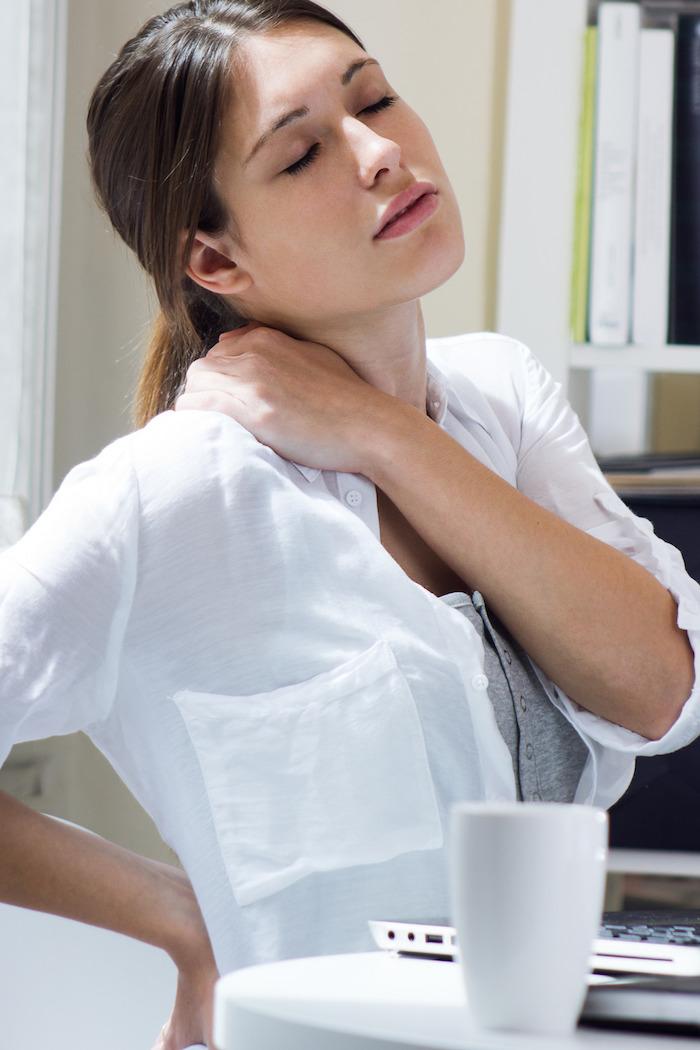 casual outfit frau im weißen hemd braune haare schmerzen im nacken muskelkater loswerden sport treiben gesundheit