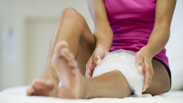 frau im pinken top eis auf das bein sport trotz muskelkater was kann man gegen muskelschmerzen tun