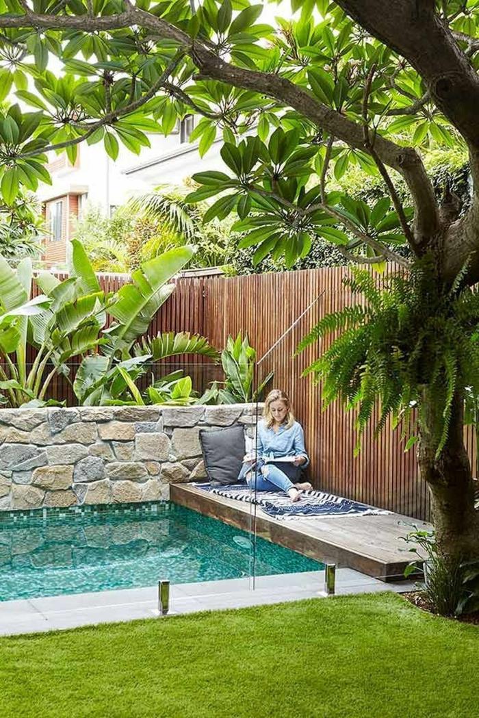 frau liest buch im garten mit pool großer grüner baum außenausstattung ideen poolgestaltung inspiration
