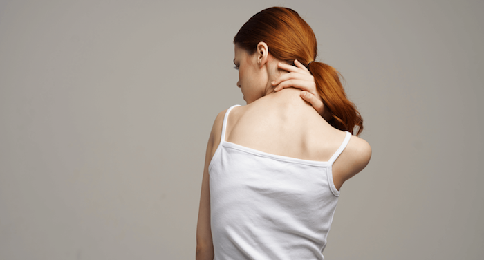 frau mit langen roten haaren weißes top schmerzen im nacken was hilft gegen muskelkater wichtige tipps und ideen