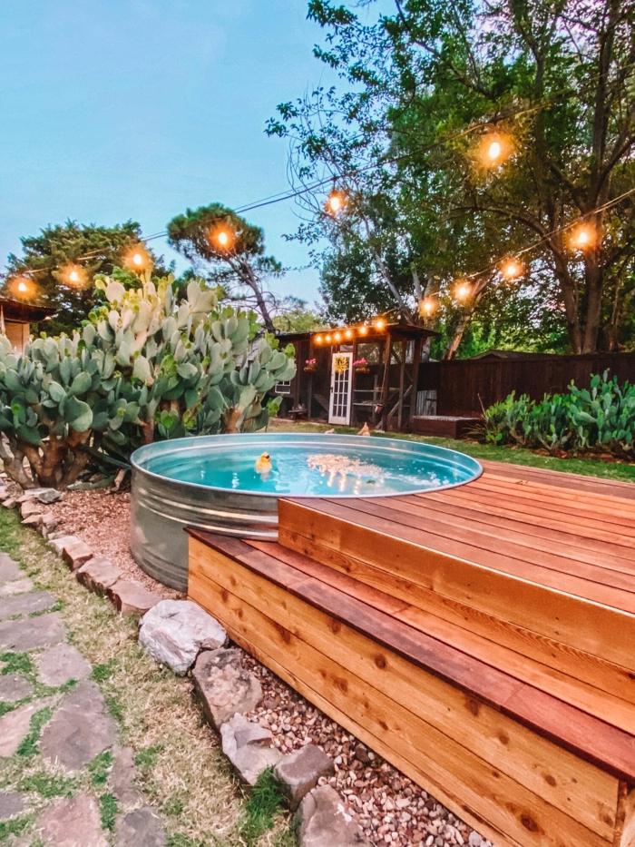 garten gestaltung ideen für poolumrandung rundpool große grüne pflanze deko spielzeug ente in einem runden schwimmbad aufgehängte kleine lichter
