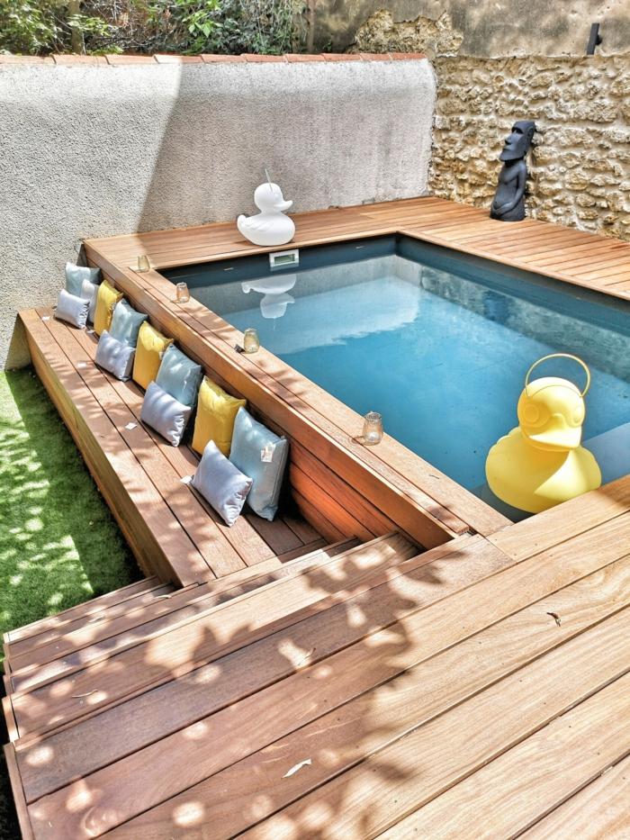 gartengestaltung terrasse höher als garten pool aus holz bunte deko kissen in gelb und grau dekorative gelbe ente im schwimmbad pool gestaltungsideen