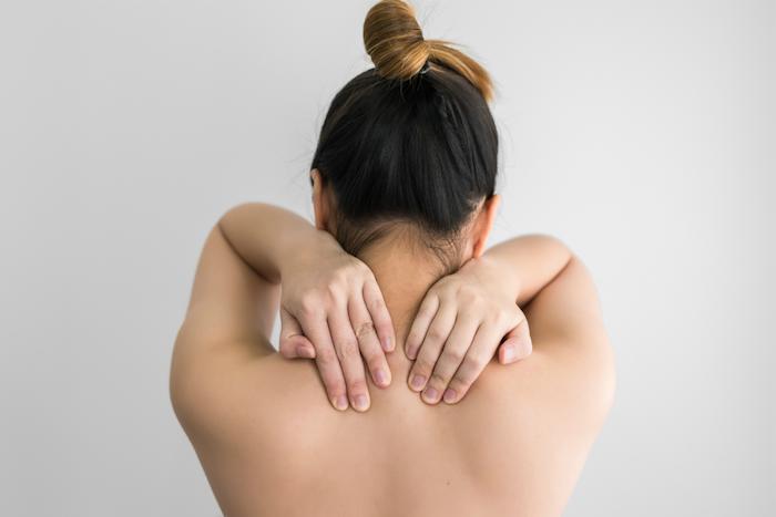 gesundheit sport trotz muskelkater frau mit schmerzen im nacken braune hochgesteckte haare