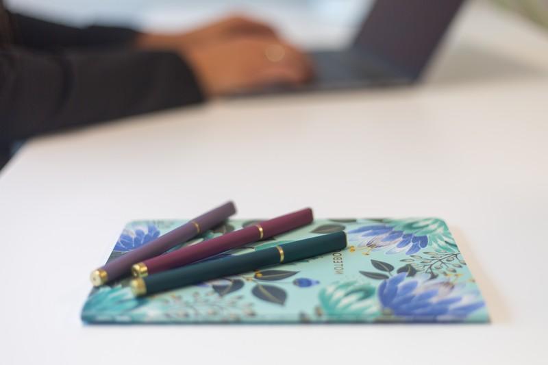giffits gmbh sachen berdrucken werbematerialien highflyerswerbeartikel bedrucken schreibtisch buntes notizbuch drei kugelschreiber grün rot lila