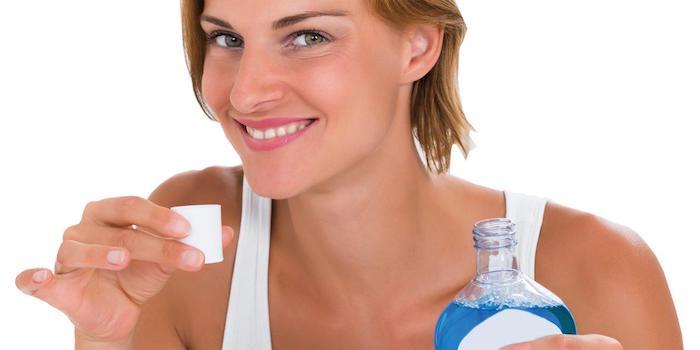 hausmittel gegen zahnschmerzen was tun bei zahnschmerzen kieferentzündung frau lächelt hält flasche mundpflege mundspülung