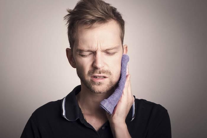 hausmittel zahnschmerzen zahnnerv beruhigen hausmittel entzündung im mund behandeln mann mit lila tuch am kiefer